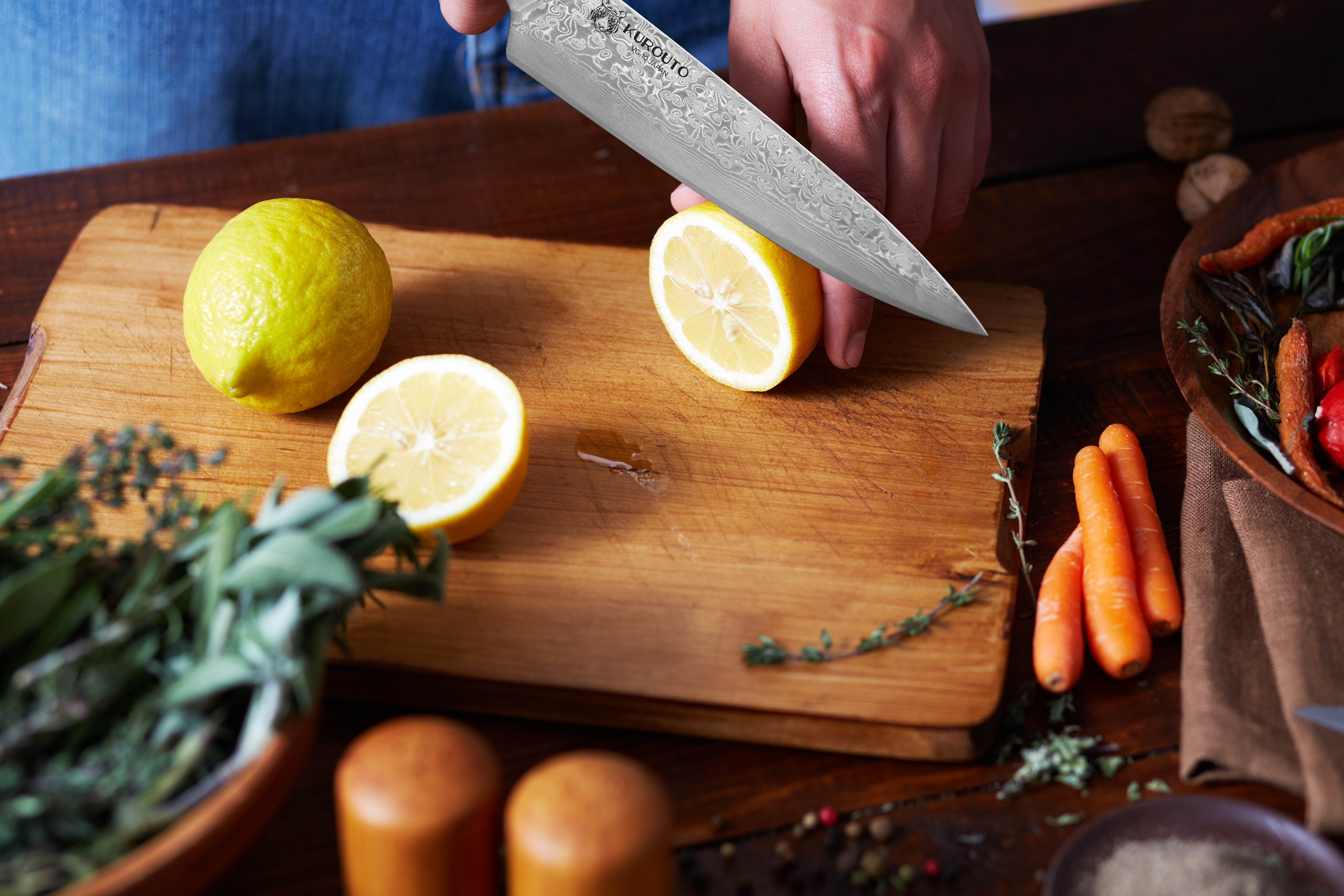 Kurouto Kitchenware Chef's Knife Slicing a Ripe Lemon on a Wooden Cutting Board