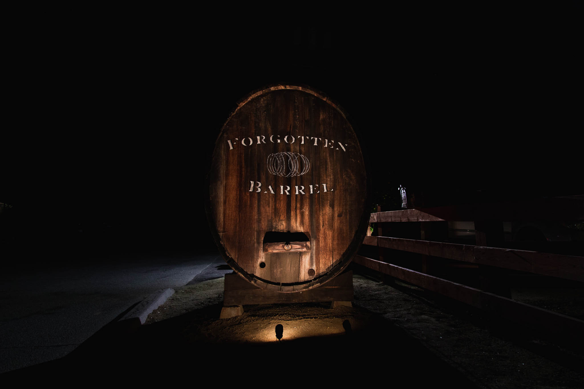 Handpainted Historic Barrel with Winery Branding Illuminated by light at night