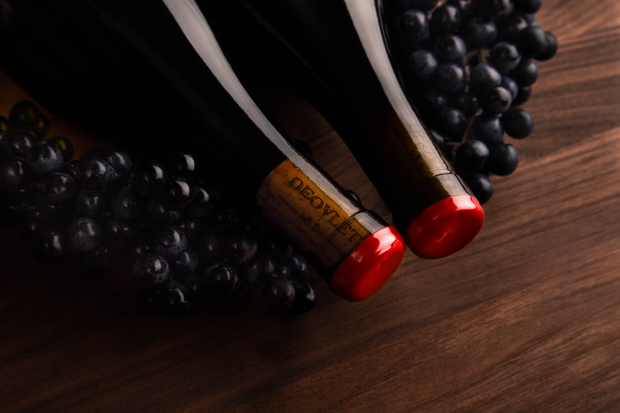 Close Up Detail Shot of San Luis Obispo Based Deovlet Wines' Corks with Red Wax Seal Among Grapes